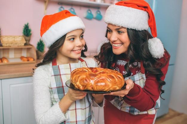 陽気で前向きな若い女性と娘が一緒に立って、お互いを見ています。彼らは笑います。女の子はクリスマスの帽子をかぶっています。 theuホールドプレートパイ付き。