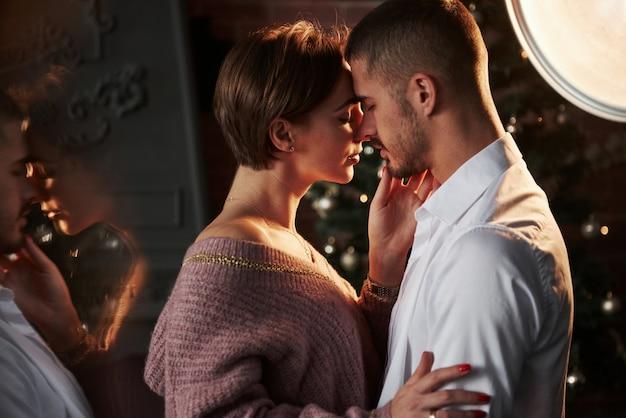 Они собираются целоваться. близость парня и девушки в роскоши одевает то, что танцует и флиртует. великолепное отражение сбоку.