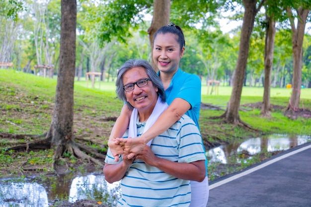 They are happy asian couple.they give a big hug together after jogging in park.