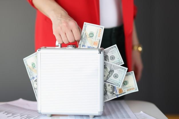 В руках серый чемодан, в котором много денег. онлайн-концепция быстрых денег