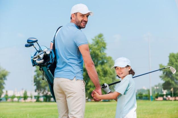 彼らはゴルフの大ファンです。幸せな若い男と彼の息子は、ゴルフコースを歩きながら手をつないでカメラを見て