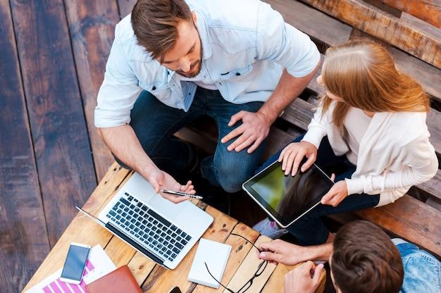 彼らはどこでも働くことができます!屋外に座って一緒に働く3人の若者の上面図