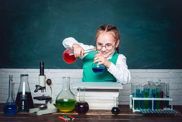 그들은 화학에서 새로운 실험을 수행했습니다. 행복한 작은 과학자는 학교와 가정 교육에 시험관을 가지고 실험을 하고 있습니다