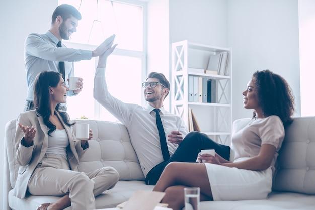彼らは少し休む価値があります。彼らの美しい同僚とオフィスでソファに座っている間ハイタッチを与え、笑顔でコーヒーカップを保持している2人のハンサムな男