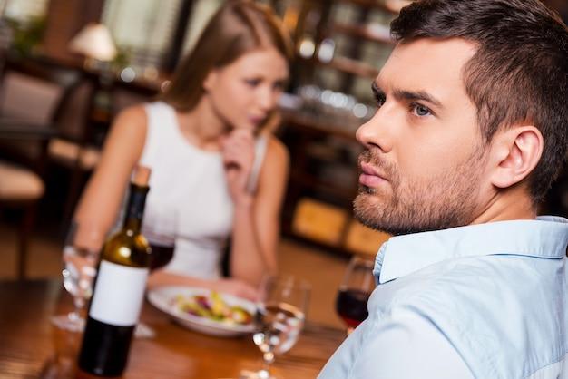 Им больше нечего сказать. разочарованный молодой человек смотрит в сторону, сидя вместе со своей девушкой в ресторане