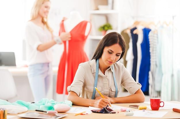 彼らは自分たちがしていることが好きです。自信を持って若い女性がスケッチしながら、別の女性が背景のドレスを測定します