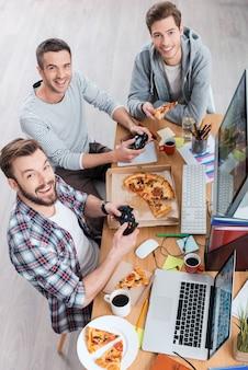 그들은 그들이하는 일을 좋아합니다. 책상에 앉아 컴퓨터 게임을 하고 피자를 먹는 세 젊은이의 상위 뷰