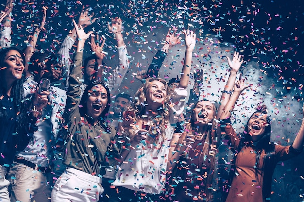 They love having fun. group of beautiful young people throwing colorful confetti and looking happy