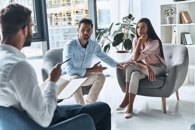 Им нужен совет. молодая супружеская пара разговаривает, сидя на сеансе терапии