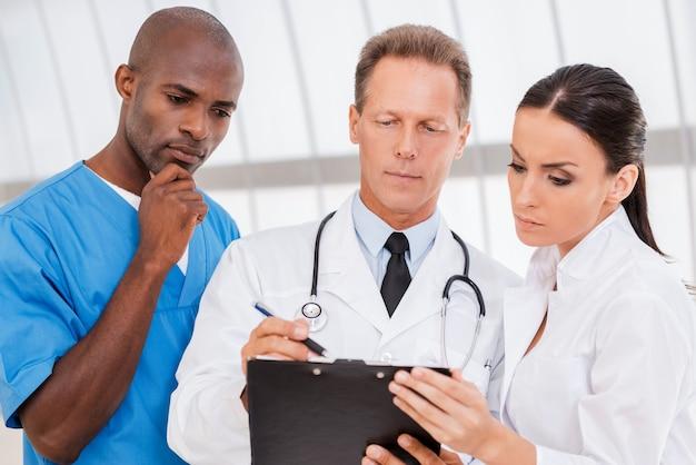그들은 전문가의 조언이 필요합니다. 남자가 클립보드에 무언가를 쓰는 동안 3명의 자신감 있는 의사가 무언가를 토론하고 있다