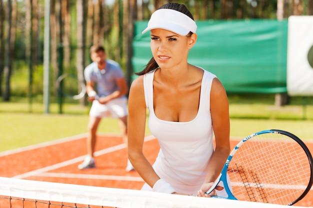 그들은 팀처럼 플레이합니다. 테니스 코트에 서서 남자와 함께 테니스 라켓을 들고 멀리 바라보는 아름다운 젊은 여성
