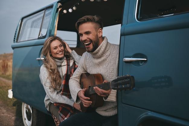 Они запомнят этот день. красивый молодой человек играет на гитаре для своей красивой подруги, сидя в синем мини-фургоне в стиле ретро