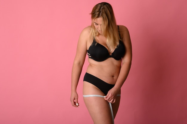 Thick beautiful woman measures waist. young beautiful woman measures your body parts of roulette