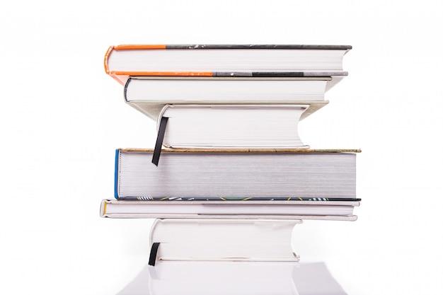 Толстые книги, изолированные на белой поверхности