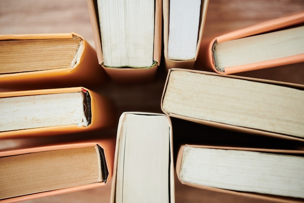 Thick books on table, view from above, selective focus