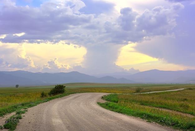 Густые кучевые облака вечером над горной равниной с сельской дорогой. сибирь, россия