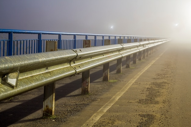 Thick fog over empty road at night