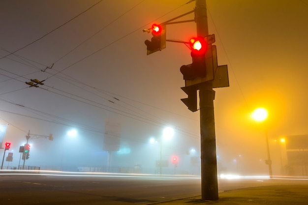 Thick fog over empty road with traffic lights at night