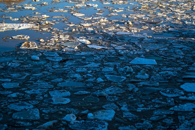 Thick ice pieces on the river in the winter thaw