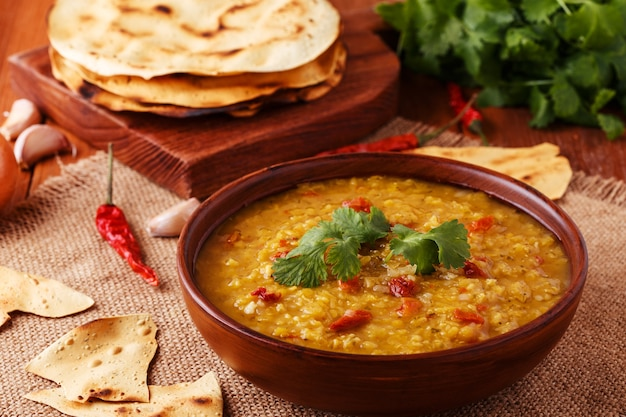 Thick indian red lentil soup with cilantro served with indian flat bread on a wooden background