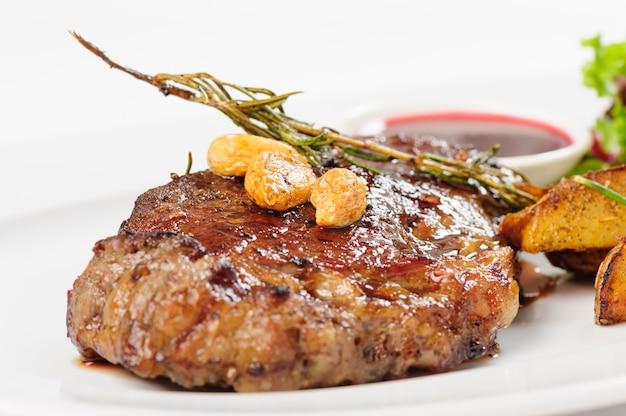 감자와 샐러드를 곁들인 두꺼운 육즙 쇠고기 스테이크