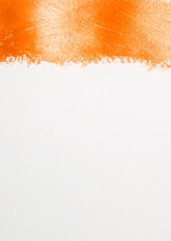 Thick line of orange paint and white background