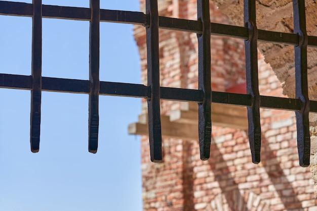 Толстая металлическая решетка, закрывающая вход в крепость на фоне голубого неба. крепость орешек в солнечный летний день