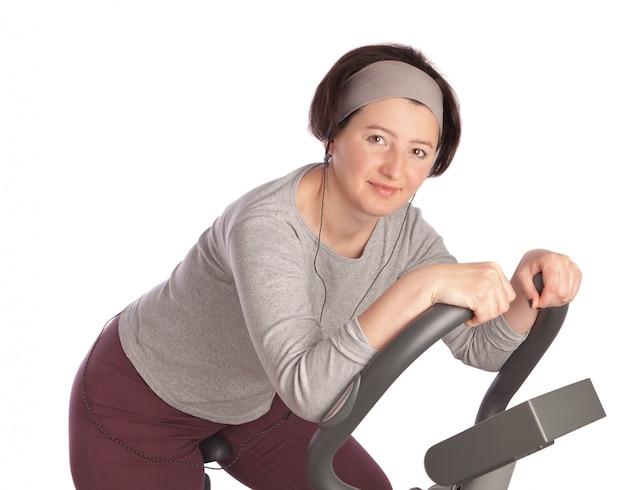 고정식 자전거에 체육관에서 두꺼운 중 년 여자. 흰 벽에.