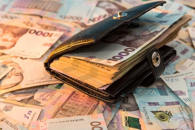 The thick money-laden black men's wallet lies against the backdrop of ukrainian hryvnia money. concept of saving money