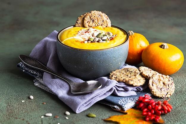 크림, 잡곡 크래커 및 씨앗을 그릇에 담은 두꺼운 호박 수프. 건강한 채식 음식.