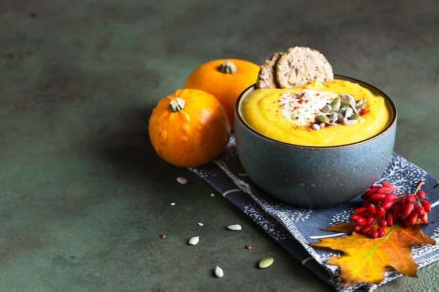 Thick pumpkin soup with cream, multigrain crackers and seeds in a bowl. healthy vegetarian food.