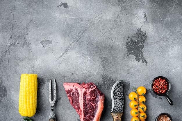 調味料とローズマリーがセットされた厚い生のtボーンステーキ、灰色の石のテーブル、上面図フラットレイ