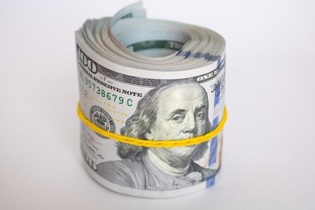 고무줄로 묶인 100달러 지폐의 두꺼운 롤