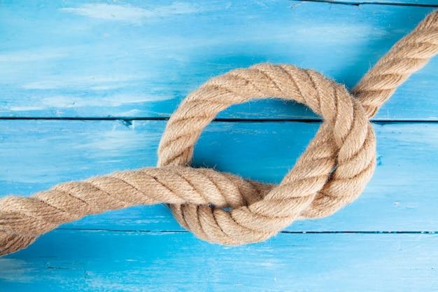 木製の青いシーンで結び目に織り込まれた太いロープ