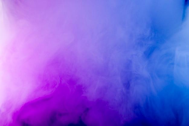 네온 불빛에 짙은 연기. 분홍색과 파란색 빛, 질감, 배경입니다. 초점없는. 추상 어두운 배경입니다.