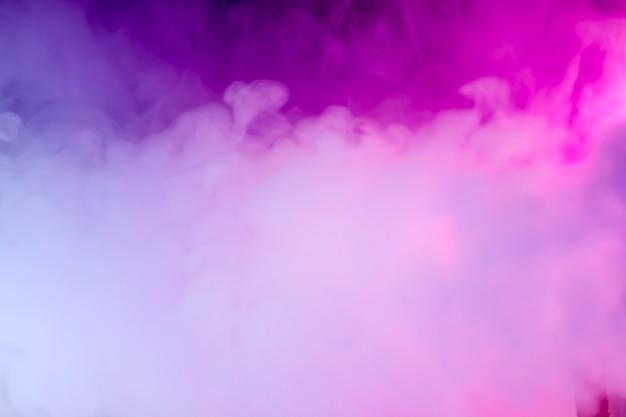 ネオンの光の中で濃い煙。ピンクとブルーの光、テクスチャ、背景。焦点が合っていない。抽象的な暗い背景。