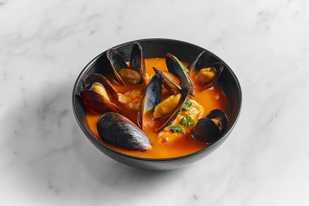 Thick tuscan cacciucco soup with seafood. classic red soup with mussels, scallops and fish in a black plate on a marble surface