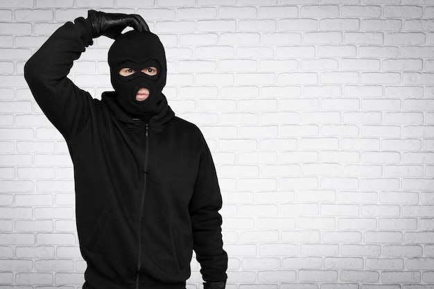 Thief in black balaclava and clothes on background