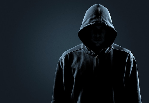 Thief in black clothes on grey background