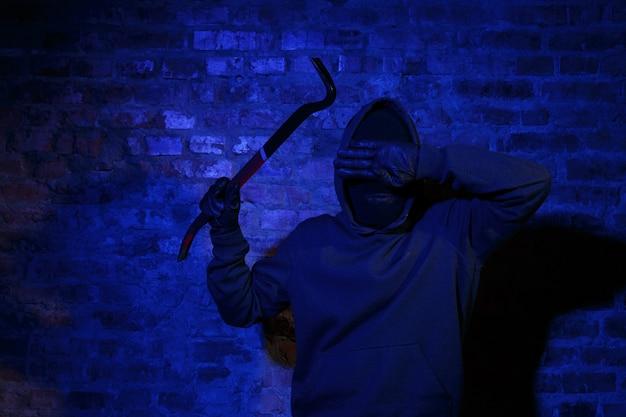 도둑은 벽돌 벽에 해골 키를 들고 손으로 눈을 감습니다