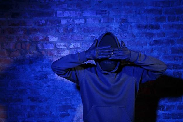 泥棒は夜にレンガの壁で彼の目を閉じる革手袋
