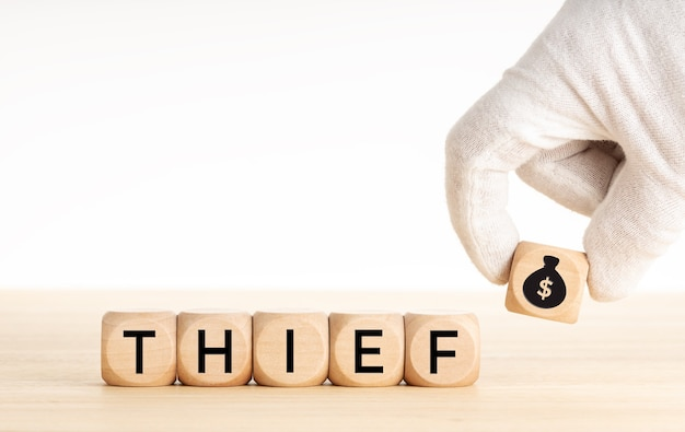 泥棒の概念。木製のブロックの聖霊降臨祭のお金の袋のアイコンと木製のサイコロのテキストを手で摘みます。スペースをコピーします。