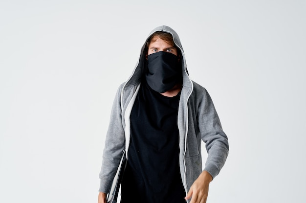 Thief in the hood covers the face of the crime theft of money anonymity
