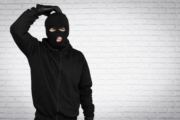 검은 balaclava와 배경에 옷을 입은 도둑