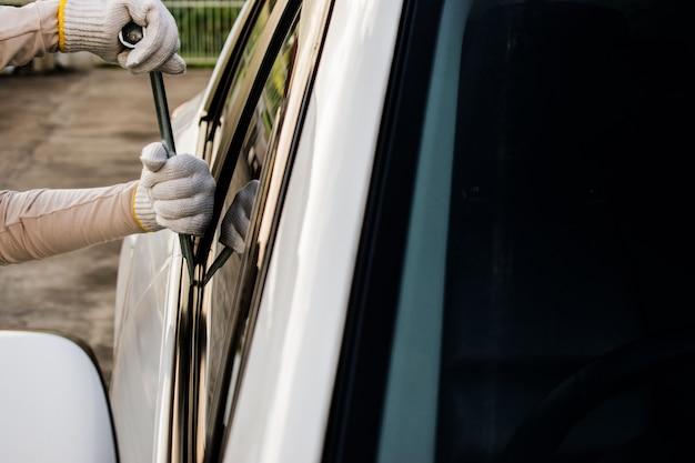 Вор пытается угнать машину. взломщик открывает дверь автомобиля, взломав