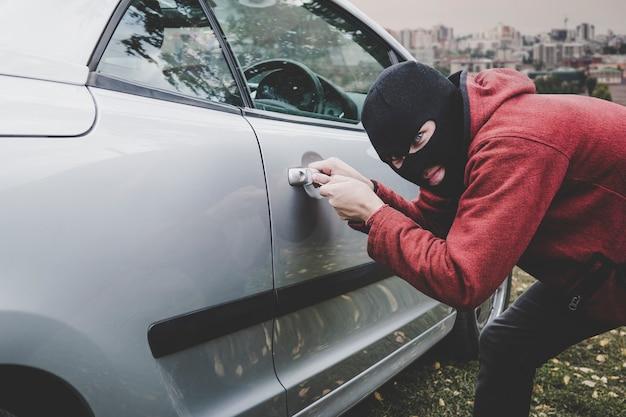 Вор смотрит в окно машины, готов что-то украсть. преступник в черной балаклаве и толстовке с капюшоном открывает чью-то машину отмычкой. неизвестный мужчина со скрытым лицом разбивает машину.