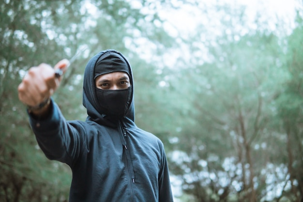 Thief in a mask and wearing black hoodie pointed the knife beside copyspace when stand at the forest