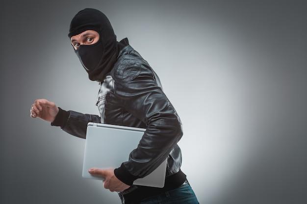 노트북 컴퓨터를 훔치는 도둑. 회색 배경에 고립