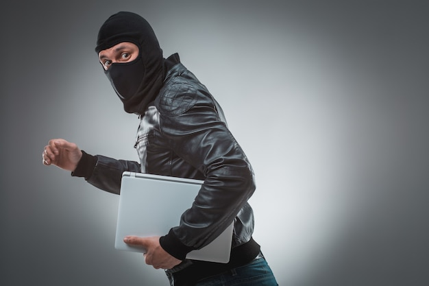 Thief stealing a laptop computer. isolated on gray background