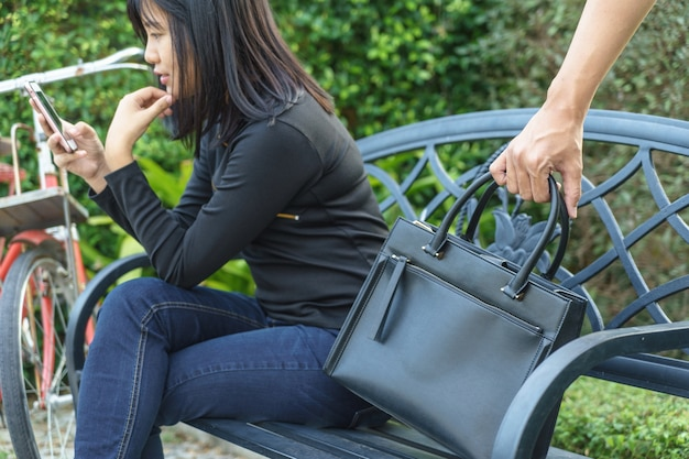 Thief trying to steal and walk away the shoulder bag while woman using mobile phone